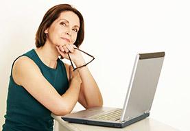 Foto einer Frau mit einem laptop, sie schaut direkt in die Kamera!